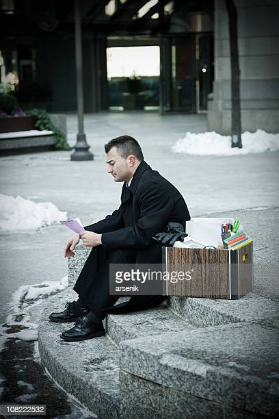 Depressed Businessman Sitting on Outdoor Stairs with Packing Box
