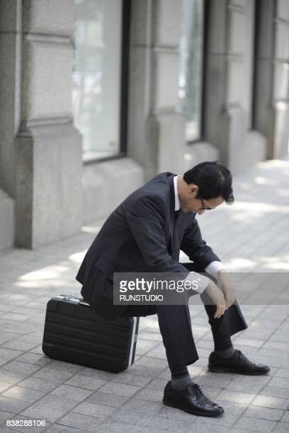 depressed businessman sitting on outdoor with his briefcase - vulnerability stock photos and pictures