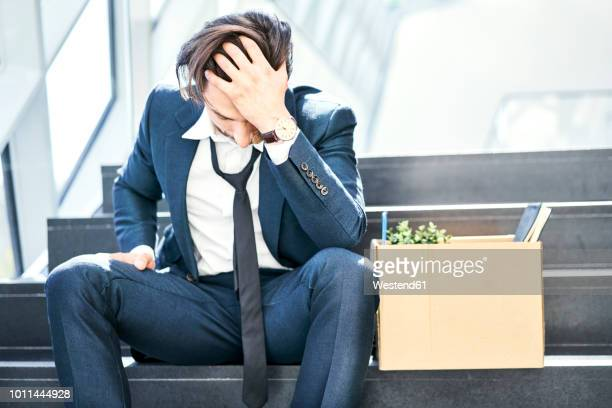 Depressed businessman sitting on stairs with belongings in cardboard box beside him