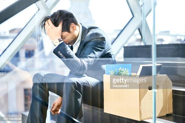 depressed businessman sitting on stairs with belongings in cardboard box beside him - downsizing unemployment stock pictures, royalty-free photos & images