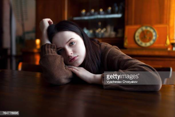 Depressed Caucasian girl leaning on table
