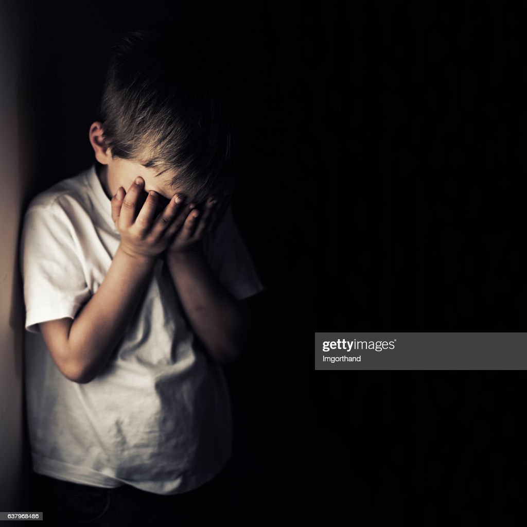 Depressed crying little boy holding head in hands : Stock Photo