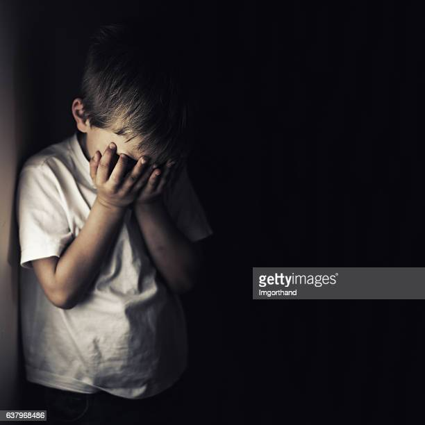 Depressed crying little boy holding head in hands