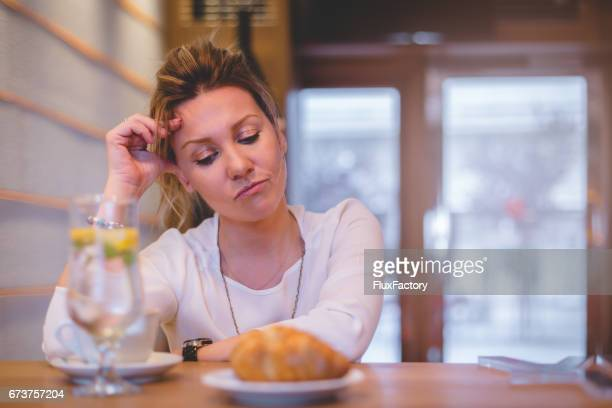 depressed female at restaurant with broken heart - negative emotion stock pictures, royalty-free photos & images