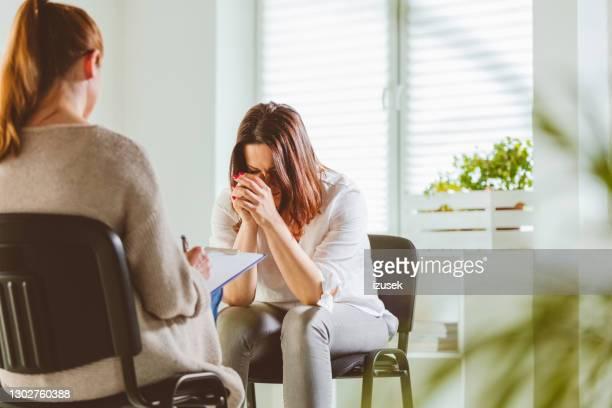 depressive frau mit psychotherapeutin - izusek stock-fotos und bilder