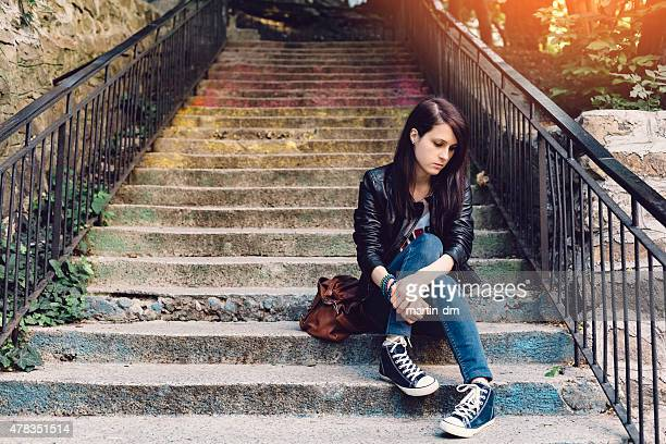 Depressed girl sitting at the staircase