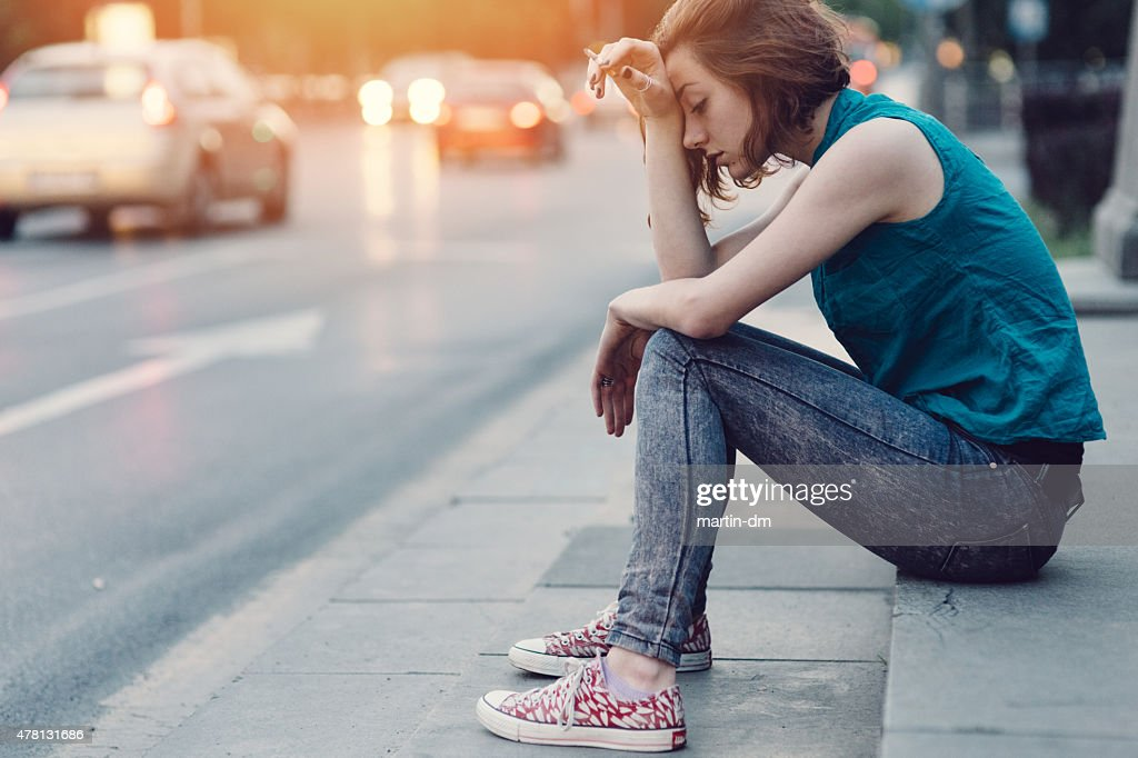 Depressed girl with cigar sitting on ground : Stock Photo