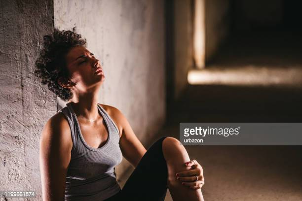 depressed helpless woman sitting alone - drug abuse stock pictures, royalty-free photos & images