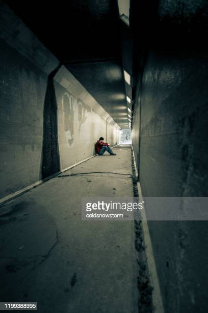 depressed homeless young man sitting in cold subway tunnel - begging social issue stock pictures, royalty-free photos & images