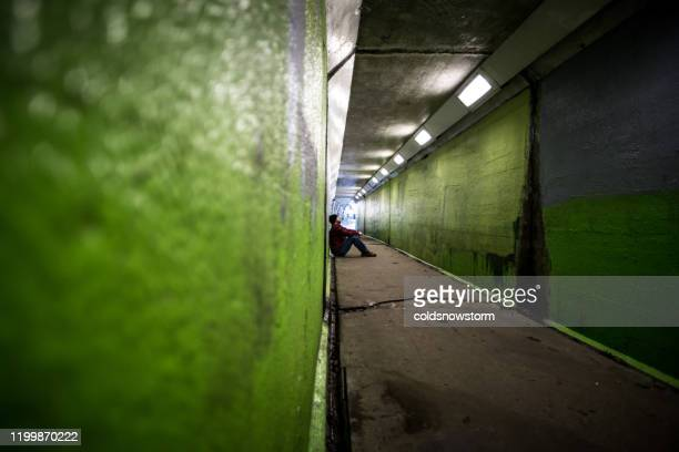 depressed homeless young man sitting in cold subway tunnel - refugee stock pictures, royalty-free photos & images
