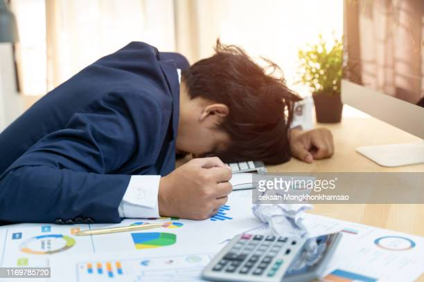 depressed investor analyzing crisis stock market with charts on laptop screen at home office - terrified stock pictures, royalty-free photos & images