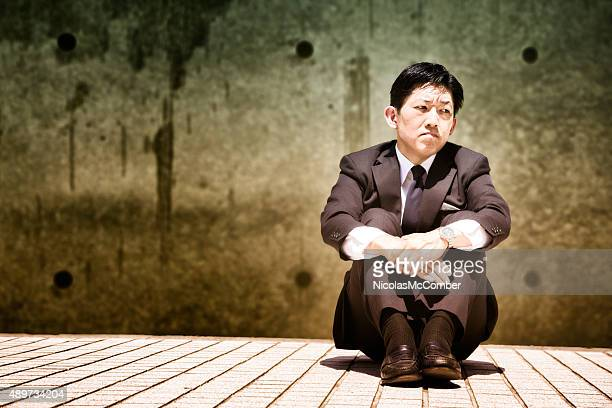 Depressed Japanese businessman sits and looks away