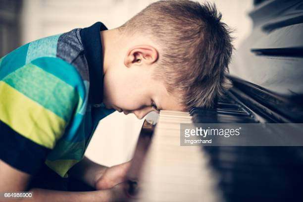 depressed little boy frustrated with his piano lesson - derrota imagens e fotografias de stock