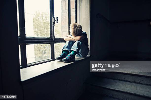 depressed little boy in old staircase - orphan stock pictures, royalty-free photos & images