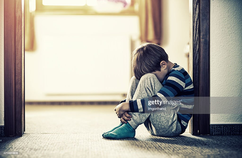 Depressed little boy sitting on the floor : Stock Photo