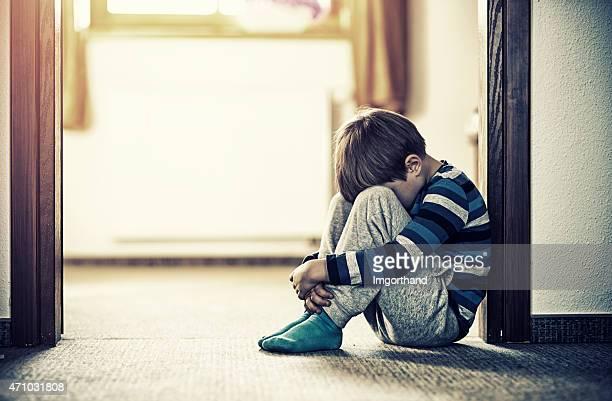 Depressed little boy sitting on the floor