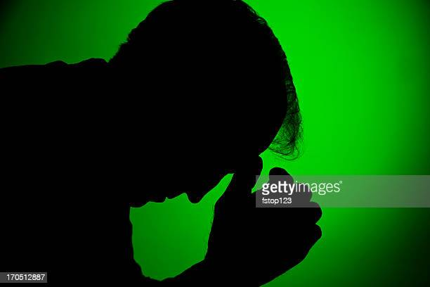Depressed man in silhouette on green