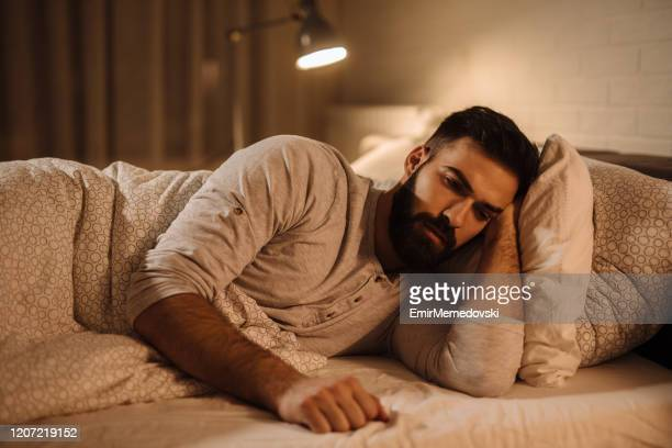 depressed man lying in his bed and feeling bad - hopelessness stock pictures, royalty-free photos & images