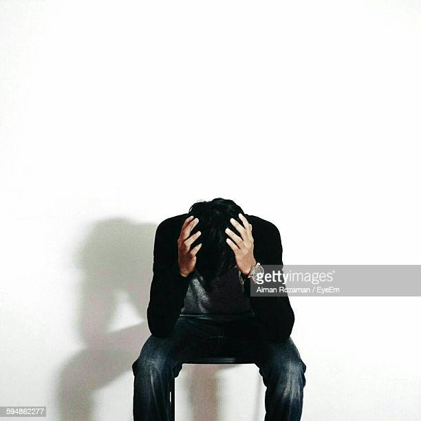 Depressed Man Sitting Against White Background