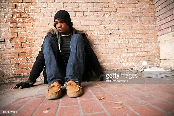 Depressed Man Sitting Among Filth