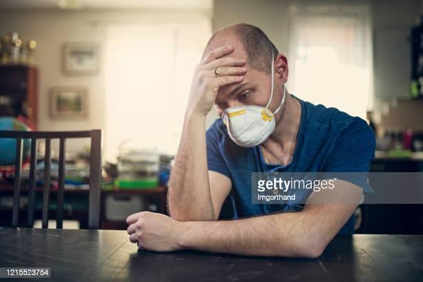 depressed man wearing anti virus mask staying at home - anti quarantine stock pictures, royalty-free photos & images