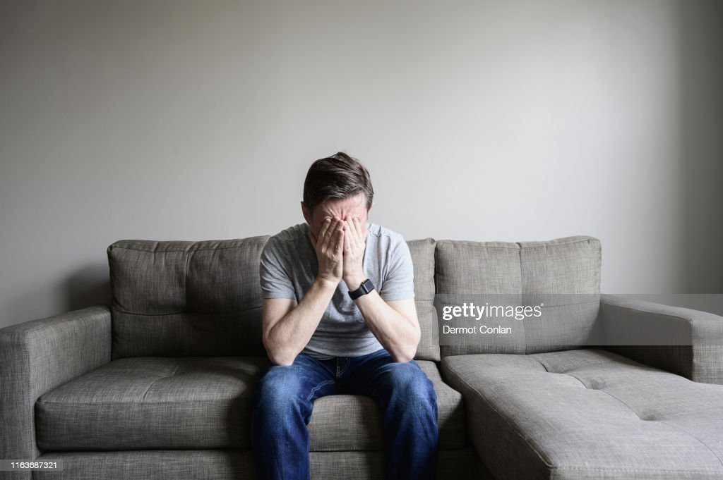 Depressed mature man sitting on couch : Stock Photo