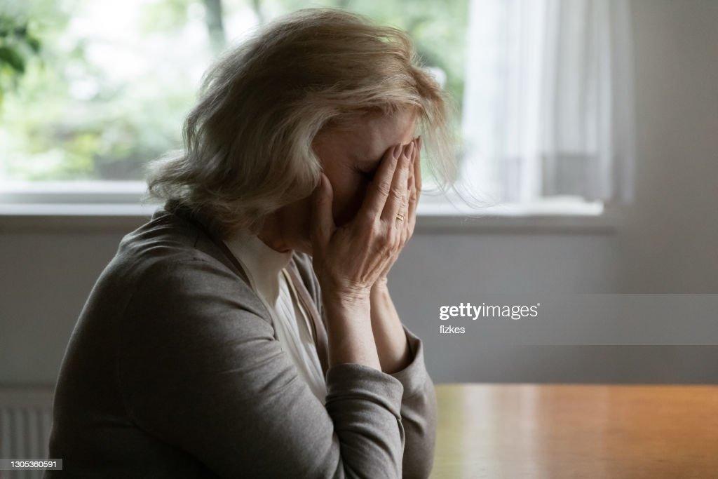 Depressed mature OAP 60s woman going through crisis : Stock Photo