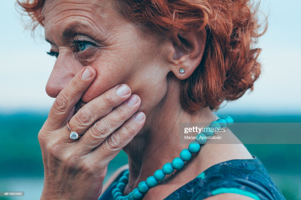Depressed mature woman feeling alone outside : Stock Photo
