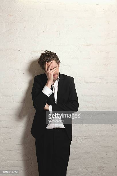 Depressed mid adult man standing against wall
