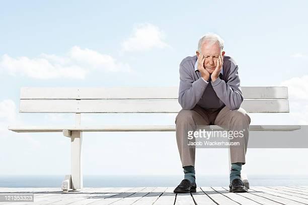 viejo hombre deprimido sentados sobre la mesa al aire libre - banco asiento fotografías e imágenes de stock