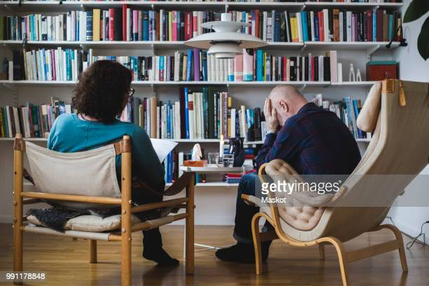 depressed patient and female therapist in front of bookshelf at home office - psychiatrist's couch stock pictures, royalty-free photos & images