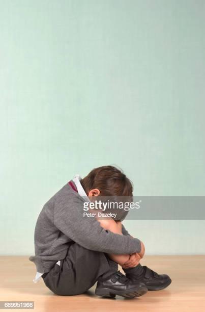 Depressed school boy sitting on the floor