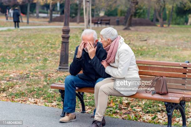 depressed senior man consoled by elderly woman - overcoat stock pictures, royalty-free photos & images
