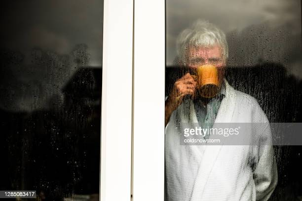 depressed senior man looking out of rainy window - looking through window stock pictures, royalty-free photos & images