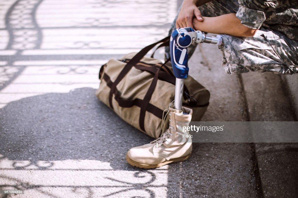 Soldado deprimido com a perna amputada, esperando o elevador : Foto de stock