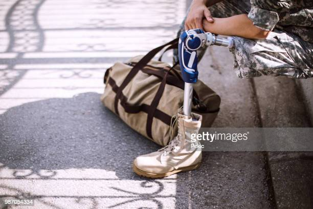 depressed soldier with amputee leg waiting for lift - us army urban warfare stock photos and pictures