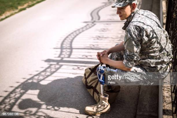 depressed soldier with amputee leg waiting for someone to pick him up - us army urban warfare stock photos and pictures