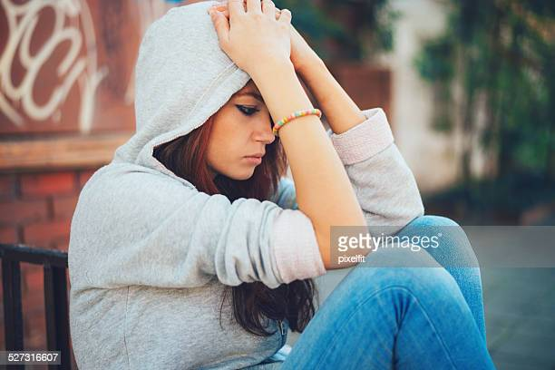 Depressed teen girl sitting lonely