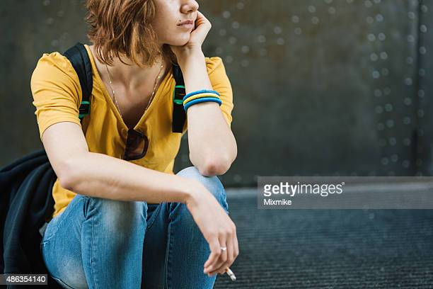 depressed teen girl smoking on stairs - little girl smoking cigarette stock photos and pictures