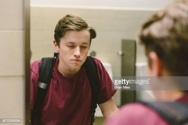 Depressed teen looks at himself in bathroom mirror