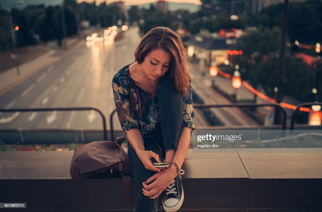 Depressed teenage girl texting on the bridge : Stock Photo