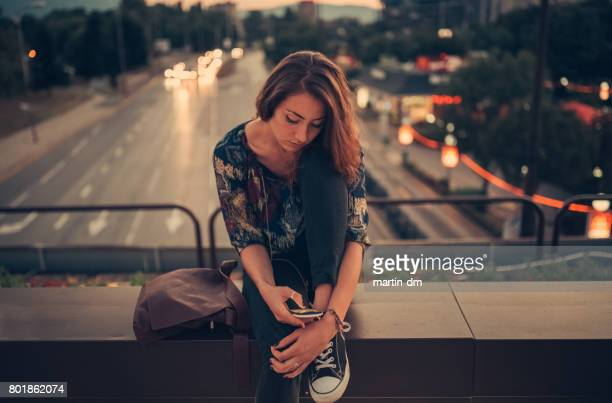 depressed teenage girl texting on the bridge - cyberbullying stock photos and pictures