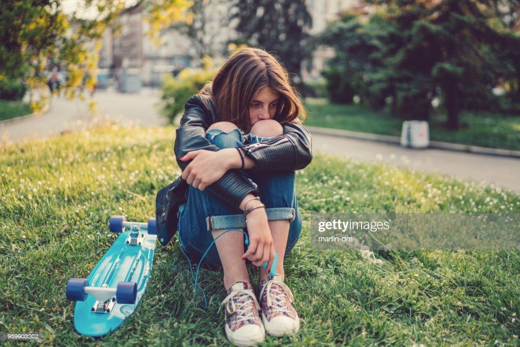 Teenager-Mädchen deprimiert mit Skateboard in der Wiese sitzen : Stock-Foto