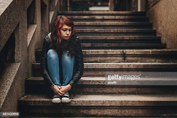 depressed teenager sitting lonely outdoors - homeless stock photos and pictures