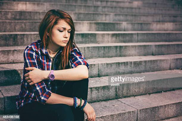 Depressed teenager sitting lonely outdoors