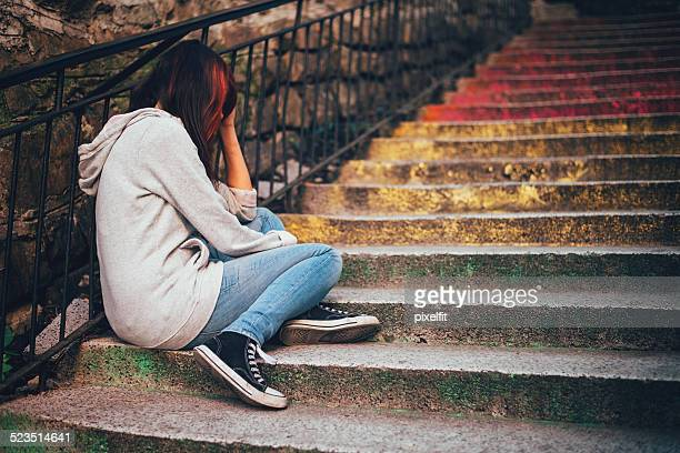 Depressed teenager sitting lonely