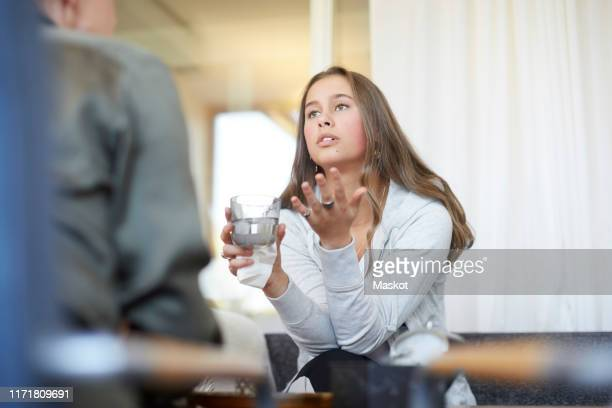 depressed teenager talking to therapist while drinking water at workshop - psychiatrist's couch stock pictures, royalty-free photos & images