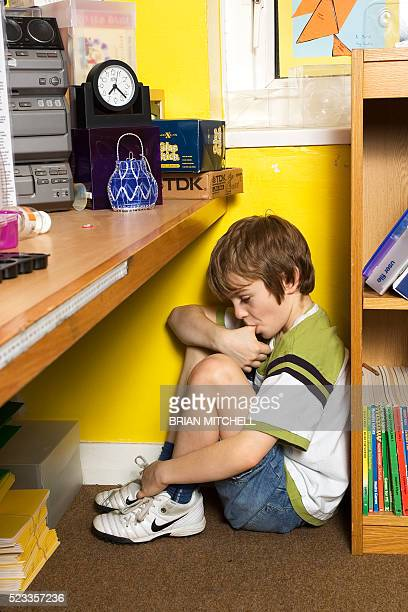 depressed & troubled six year old boy in a school class room - autism stock pictures, royalty-free photos & images