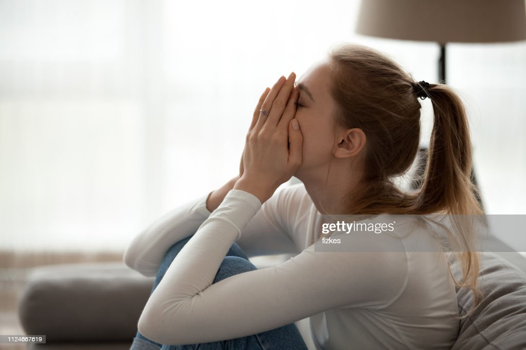 Depressed upset young woman crying alone at home : Stock Photo