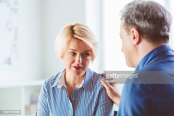 mujer deprimida discutiendo con terapeuta - izusek fotografías e imágenes de stock